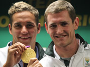 South Africa`s swimmers Chad le Clos, with Cameron van der Burgh, poses with his Olympic gold medal during their arrival at OR Tambo International Airport in Johannesburg.
