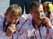 Czech Republic`s Daniel Havel, and Likas Trefil, bite the bronze medals they won in the bronze medal men`s kayak four 1000m in Eton Dorney, near Windsor, England, at the 2012 Summer Olympics.