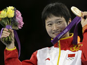 Gold medalist China`s Wu Jingyu celebrates on the podium during the medal ceremony for the women`s 49-kg taekwondo competition at the 2012 Summer Olympics.