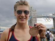 United States` rower Kara Kohler holds her bronze medal in front of the tower bridge, at the 2012 Summer Olympics.